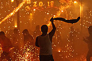 A Mexican man waves his shirt to attract the attention of the rocket launchers as dozens of sky rockets explode around him in the chaos of the Alborada festival September 29, 2018 in San Miguel de Allende, Mexico. The unusual festival celebrates the cities patron saint with a two hour-long firework battle at 4am representing the struggle between Saint Michael and Lucifer.