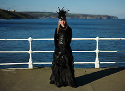 © Licensed to London News Pictures. <br /> 01/11/2014. <br /> <br /> Whitby, Yorkshire, United Kingdom<br /> <br /> Sally Betts from Leicester poses for a picture on the sea wall during the Whitby Goth Weekend. <br /> <br /> The event this weekend brings together thousands of extravagantly dressed followers of Victoriana, Steampunk, Cybergoth and Romanticism who all visit the town to take part in celebrating Gothic culture. This weekend marks the 20th anniversary since the event was started by local woman Jo Hampshire.<br /> <br /> Photo credit : Ian Forsyth/LNP