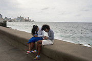 Two young women and their mobile phones by the sea, in Havana, Cuba.