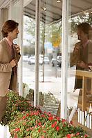 Businessman adjusting tie in shop window