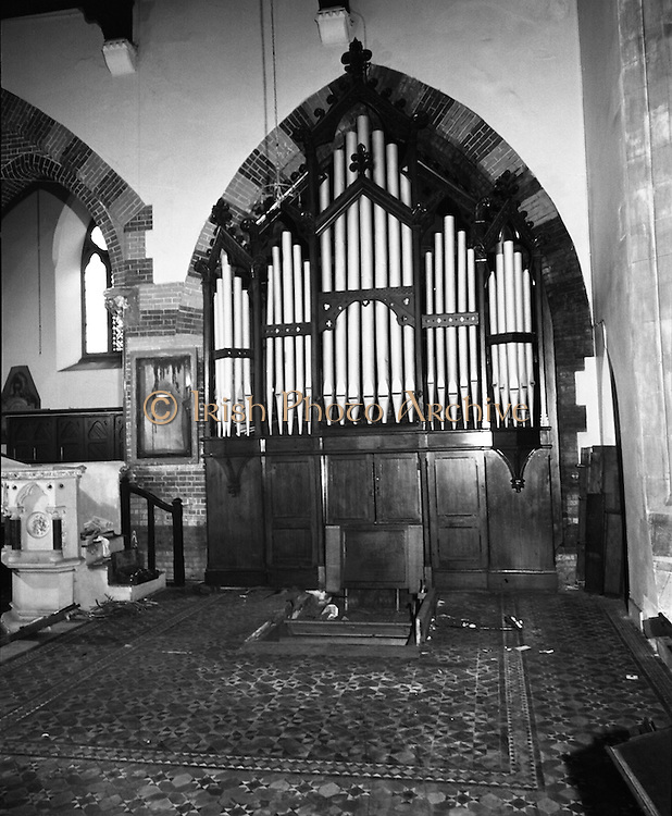 Pipe Organ Dismantling at Aungier Street.  (K86).1977..01.02.1977..02.01.1977..1st February 1977..A pipe organ built around 100 years ago for St Peter's Church (Church of Ireland),at Whitefriar / Aungier Street was being dismantled by Mr Gerry Smith and Mr Sam Wright of Dublin Organ Works. The organ was being dismantled for transfer to St Michael's Church,(Roman Catholic),in Blackrock,Co Cork..Picture shows the organ in position in St Peter's Church before being dismantled.