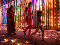 PUSHKAR, INDIA - CIRCA NOVEMBER 2018: Family walking in the Pushkar Ghats during the opening ceremonies of the Camel Fair. It is one of the world's largest camel fairs. Apart from the buying and selling of livestock, it has become an important tourist destination. The city of Pushkar is a pilgrimage site for Hindus and Sikhs.