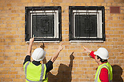 Rear view of two male workers in hardhats pointing towards windows