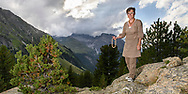 Susanne Rösli is posing on a rock with a handcrafted necklace in her hand on a cloudy summer evening in July with the Piz Ela and Rugnux in the background, Parc Ela, Grisons, Switzerland