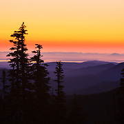 The sun rises over the Cascade Mountains and Pudget Sound during spring inversion.