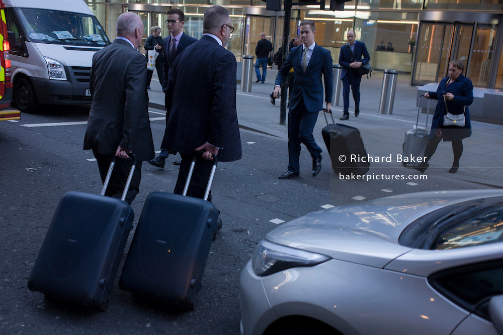 Businessmen and others tow baggage as they cross Fenchurch Street in the City of London.