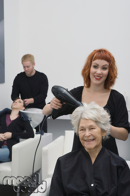 Stylist blow-drys elderly woman's hair
