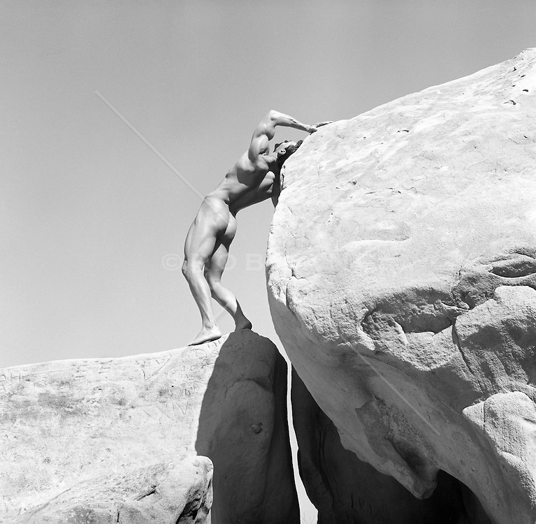 male nude posing on large rocks in the California desert