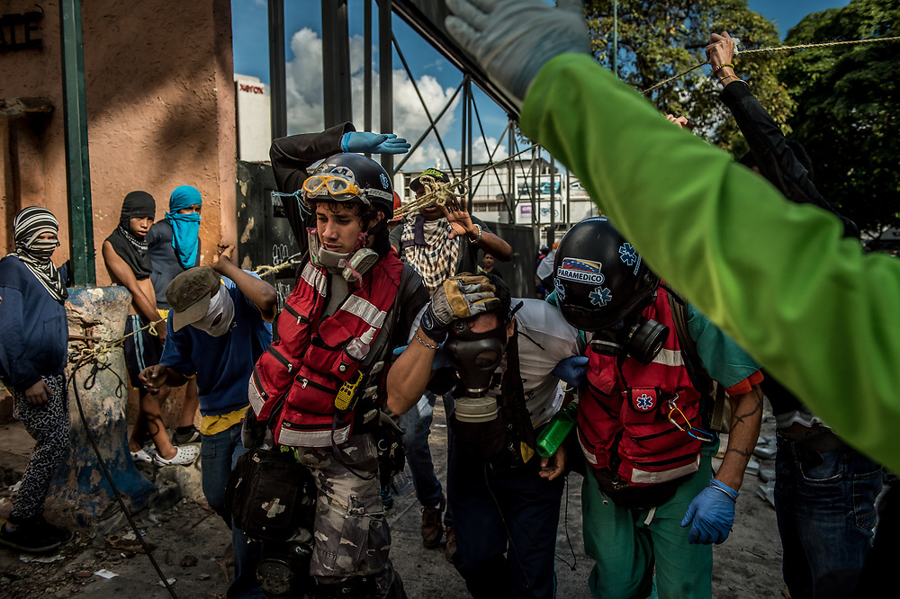 CARACAS, VENEZUELA - JULY 26, 2017: Volunteer paramedics assist a protester with a head injury, during an anti-government protest to demand that the National Constituent Assembly election scheduled for Sunday, July 30th be cancelled. The political opposition called for a 48 hour national strike on July 26th and 27th, and for their supporters to close businesses, not go to work, and instead create barricades to block off their streets.  Opposition controlled areas of the country were completely shut down.  The strike was called as part of the opposition's civil resistance movement - that began on April 1st, to protest against the Socialist government's attempt to elect a new assembly that will have the power to re-write the constitution, and their opposition to the Socialist's continued threats to Venezuelan Democracy.  PHOTO: Meridith Kohut for The New York Times