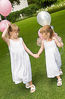 Two young girls walking in garden holding balloons