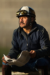 Exercise rider Bartolo Morales reads over the racing program for Churchill Downs after workouts Tuesday, April 30, 2013 at Churchill Downs in Louisville. Photo by Jonathan Palmer
