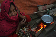 Rabia Khatun (52) is warming herself up and cooking food in front of a fire in her makeshift camp at the outskirts of Delhi State of India. More than 10,000-numbers of Burmese Rohingya Muslim refugee took shelter in Indian (Hyderabad) Andhra Pradesh, (Mewat) Haryana, (Kanchankunj) Delhi and Jammu States after ethnic strife between Rohingya Muslims and Buddhists that had been started since 1940s. Still so many peoples of aforesaid community have been living at various refugee camps in Myanmar, Bangladesh and India chiefly. Rohingya Muslims of Buthidaung, Rathedaung and Sittwe of Rakhine (formerly, Arakan) State, who ran away from Myanmar (that is, Burma) to Bangladesh to India and others South-Asian countries to escape socio-political-religious violence. (Photo/Shib Shankar Chatterjee)
