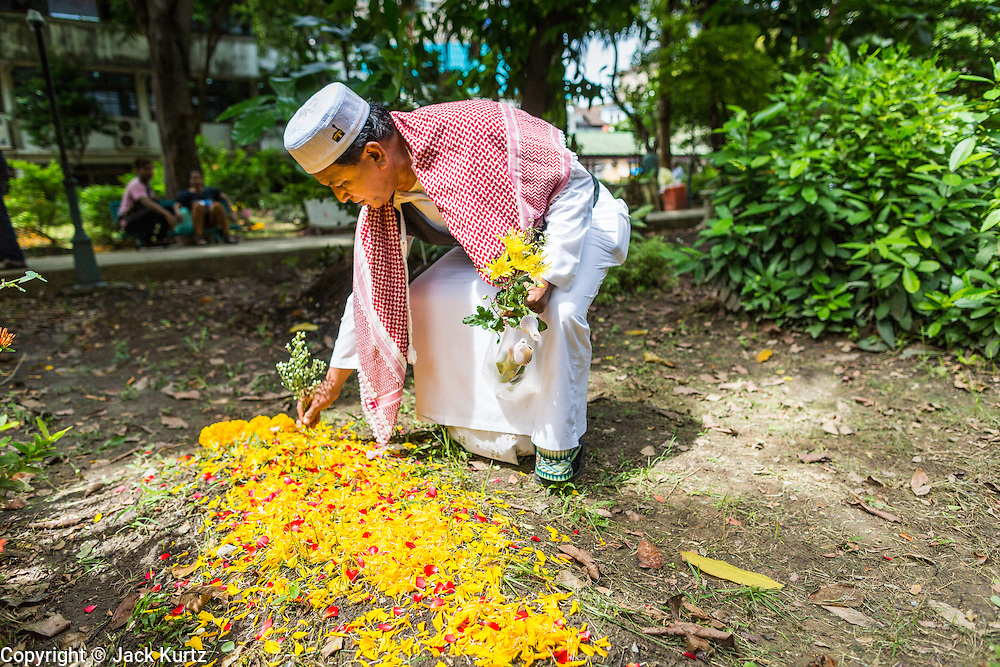 "08 AUGUST 2013 - BANGKOK, THAILAND: A man tends to his wife's grave in the Muslim cemetery next to Haroon Mosque after Eid al-Fitr services in Bangkok. Tending graves is a tradition on Eid. Eid al-Fitr is the ""festival of breaking of the fast,"" it's also called the Lesser Eid. It's an important religious holiday celebrated by Muslims worldwide that marks the end of Ramadan, the Islamic holy month of fasting. The religious Eid is a single day and Muslims are not permitted to fast that day. The holiday celebrates the conclusion of the 29 or 30 days of dawn-to-sunset fasting during the entire month of Ramadan. This is a day when Muslims around the world show a common goal of unity. The date for the start of any lunar Hijri month varies based on the observation of new moon by local religious authorities, so the exact day of celebration varies by locality.      PHOTO BY JACK KURTZ"