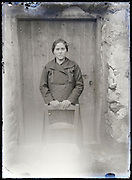 eroding glass plate photo of young adult woman in front of a closed door