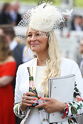 © Licensed to London News Pictures. 08/04/2016. Liverpool, UK. An elegant looking woman enjoys a drink on Ladies Day at the Grand National 2016 at Aintree Racecourse near Liverpool. The race, which was first run in 1839, is the most valuable jump race in Europe. Photo credit : Ian Hinchliffe/LNP