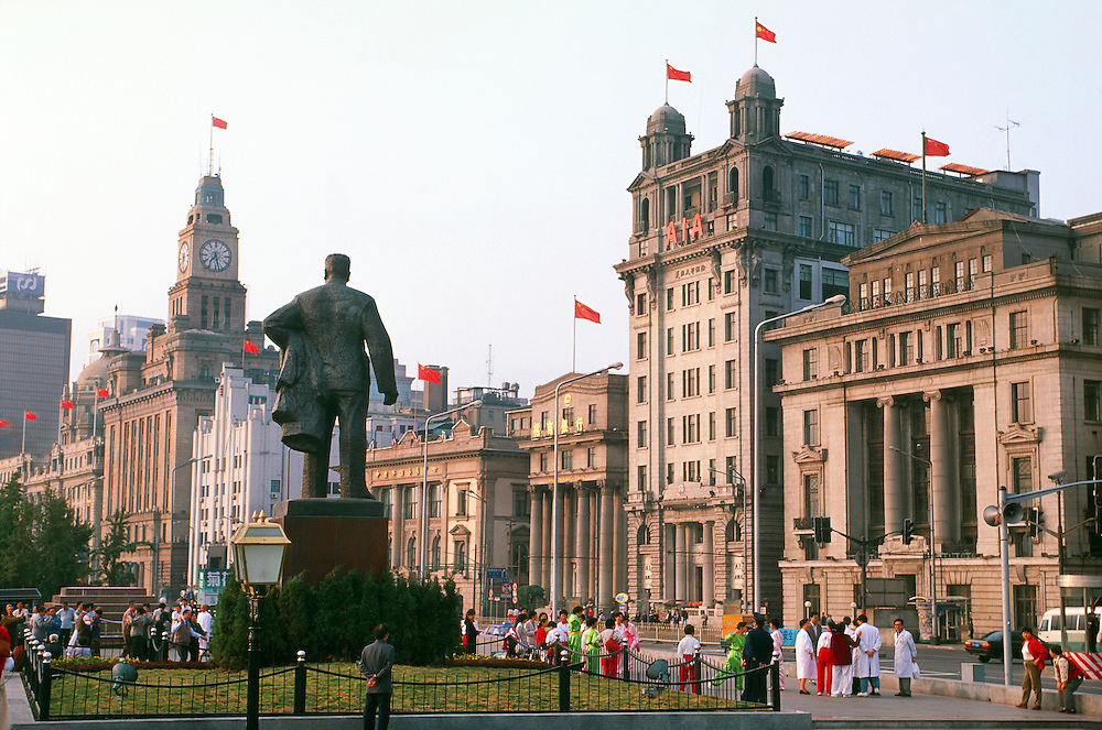 Early morning exercisers in Huangpu Park near a statue of Mao Zedong (The Bund in background),  Shanghai, China