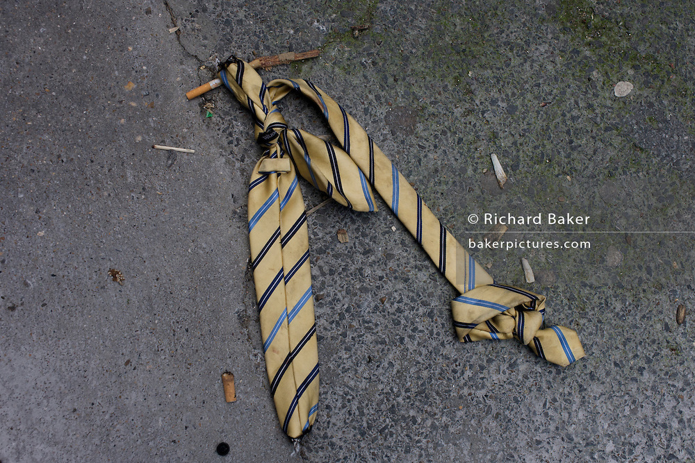 An unwanted necktie lies still knotted in a central London street.