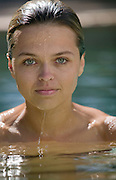 Beautiful Woman in pool, looking at camera