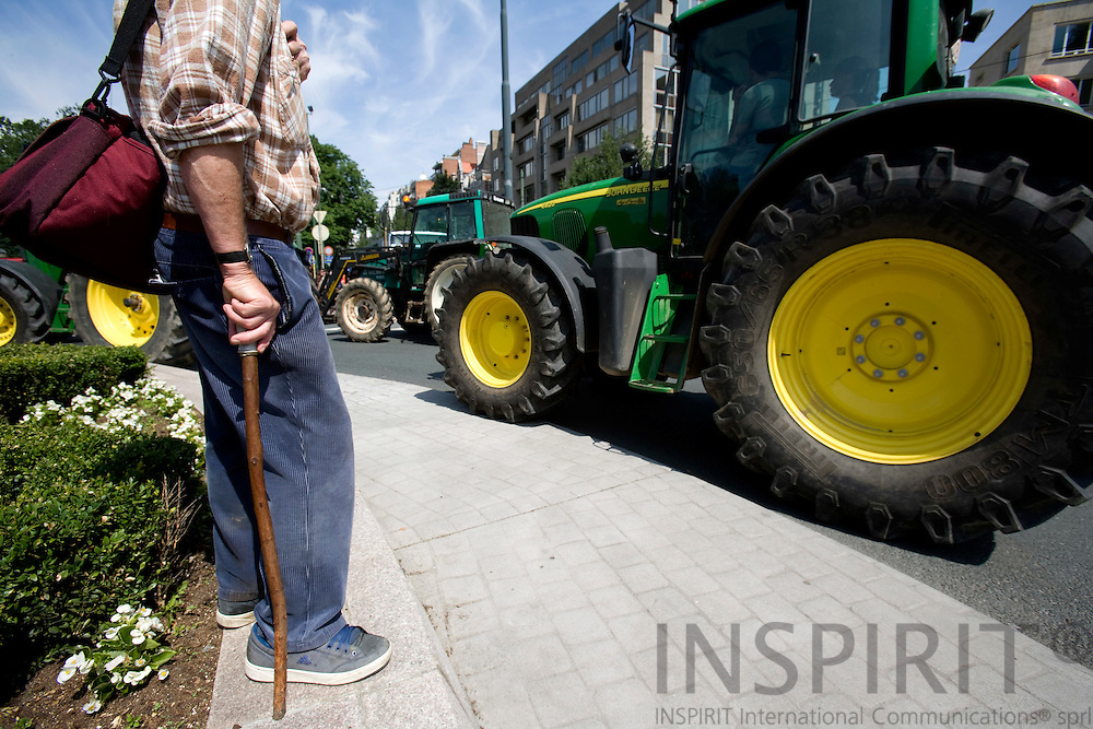 BRUSSELS - BELGIUM - 18 JUNE 2008 -- Hundreds of Farmers from belgian Wallonia went with their tractors to brussels to protest against high fuel cost the day before an EU summit to push leaders for help coping with skyrocketing fuel prices. Here tractors passing an man with a stick in a roundabout with flowers.  Photo: Erik Luntang