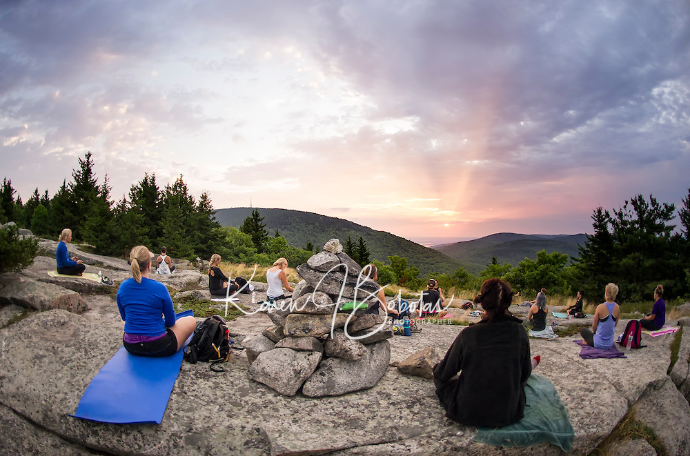 Kelli Powers and Laurel Brauns join Kate Criscone from Body Design by Joy as she leads her group in a sunrise yoga class from the top of Piper Mountain on Saturday morning.  (Karen Bobotas/for the Laconia Daily Sun)