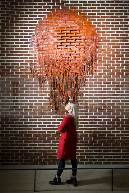 © Licensed to London News Pictures. 29/03/2017. Wakefield UK. Mille Carroll looks at the new melted wax art work by Alex Chinneck called A Hole in a Bag of Nerves which is in the Re-constuct exhibition at Yorkshire Sculpture Park. The Yorkshire Sculpture Park has two new exhibitions drawn from the Arts Council Collection. The Re-Construct exhibit featuring Cornelia Parker & Alex Chinneck & the Kaleidoscope exhibition, a new Arts Council Collection touring exhibition. Photo credit: Andrew McCaren/LNP