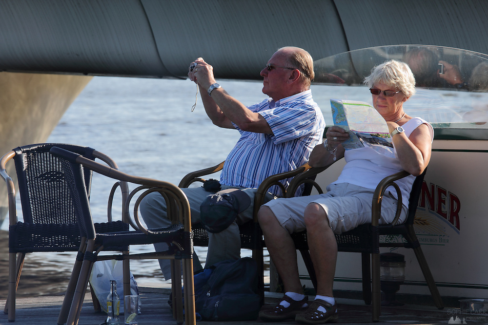 A man takes a photograph of the windmills at Zaanse Schans while his wife looks at the map, north of Amsterdam
