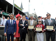 Actor and Longines Ambassador of Elegance Simon Baker, left, joins Jennifer Judkins, second left, and Juan-Carlos Capelli, third left, both of Longines, to award trainer Steve Asmussen, jockey Rosie Napravnik and owner Ron Winchell, left to right, with their Longines timepieces after their horse Untapable won the Longines Kentucky Oaks on Kentucky Oaks Day, Friday, May 2, 2014, in Louisville, Ky.  Longines, the Swiss watch manufacturer known for its luxury timepieces, is the Official Watch and Timekeeper of the 140th annual Kentucky Derby. (Photo by Diane Bondareff/Invision for Longines/AP Images)