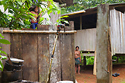 An Embera man and woman stare on as a crude gravity flow faucet leaks, Churoco, Darien Province, Panama.