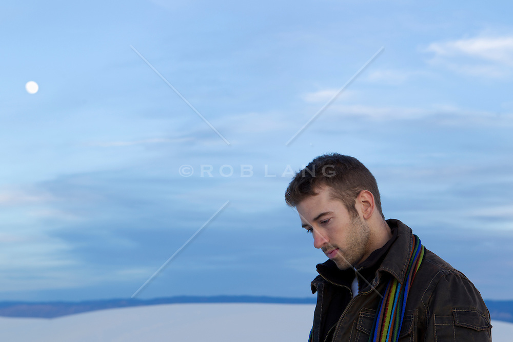 man looking down while a full moon rises over a sand dune in White Sands, NM