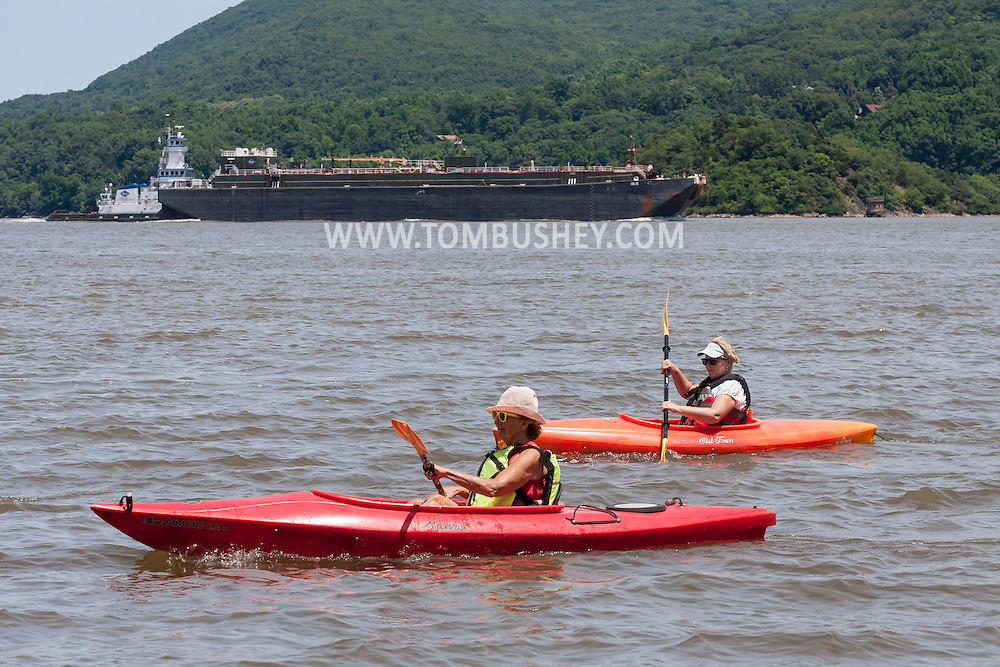Cornwall-on-Hudson, New York - Two women paddle kayaks as a tugboat pushes a barge south on the Hudson River in a view from Cornwall Landing on June 20, 2014. ©Tom Bushey / The Image Works
