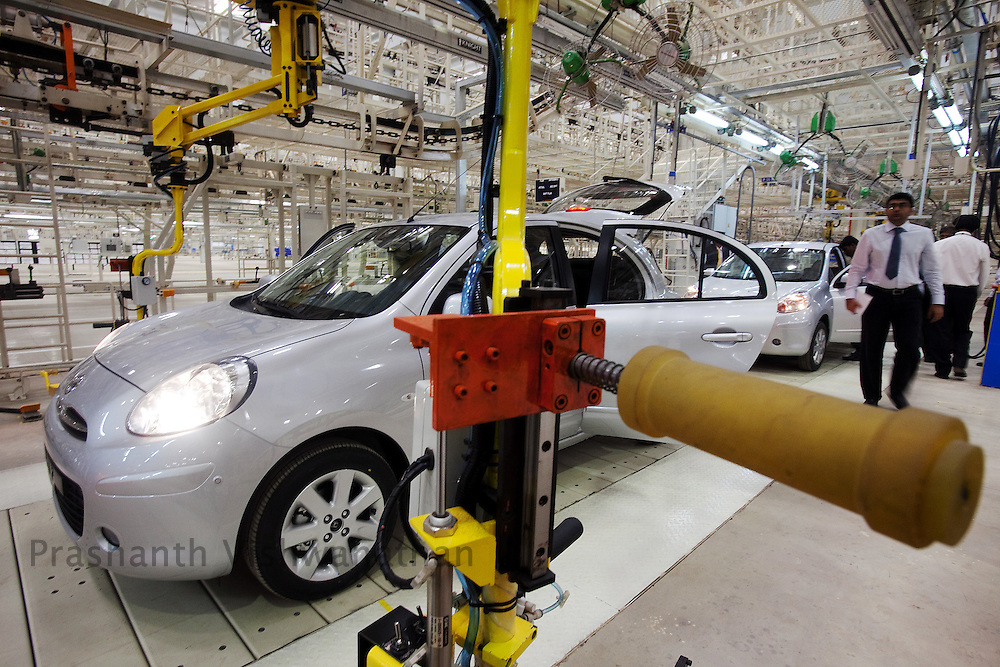 Dignitaries and media personell inspect the newly made Nissan Micra car in an assembly line in the Renault Nissan Alliance plant during its inaugration, in the outskirts of Chennai, India, on Wednesday, March 17, 2010. Photographer: Prashanth Vishwanathan/Bloomberg