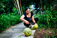 A woman cracks open fresh coconuts on the side of a small path in a village in the Mekong Delta in southern Vietnam.