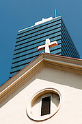 An old church and crucifix in front of a modern building in downtown Honolulu, Hawaii.