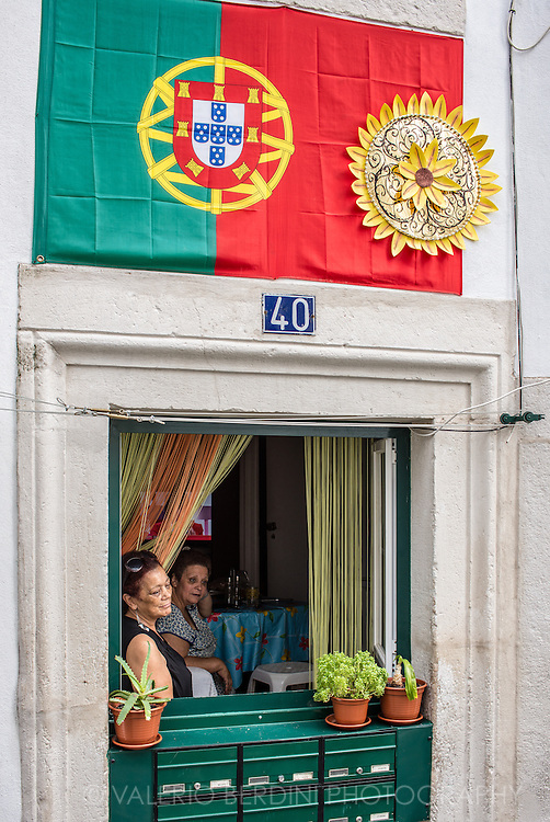 Two women look on the street from the window of their apartment in the labirinthine streets of Alfama. A Portoguese flag is on the wall.
