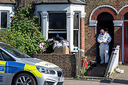 © Licensed to London News Pictures. 25/04/2020. London, UK. A forensic investigator wearing a protective suit and facemask walks through a doorway to a property at the scene of a fatal house fire. A man has died in a house fire in Earlsfield, Wandsworth. Firefighters found the man in a ground floor bedroom. He was brought out of the property by fire crews but he died at the scene. London Fire Brigade was called at 07:36 BST and the fire was under control by 08:33 BST. Photo credit: Peter Manning/LNP