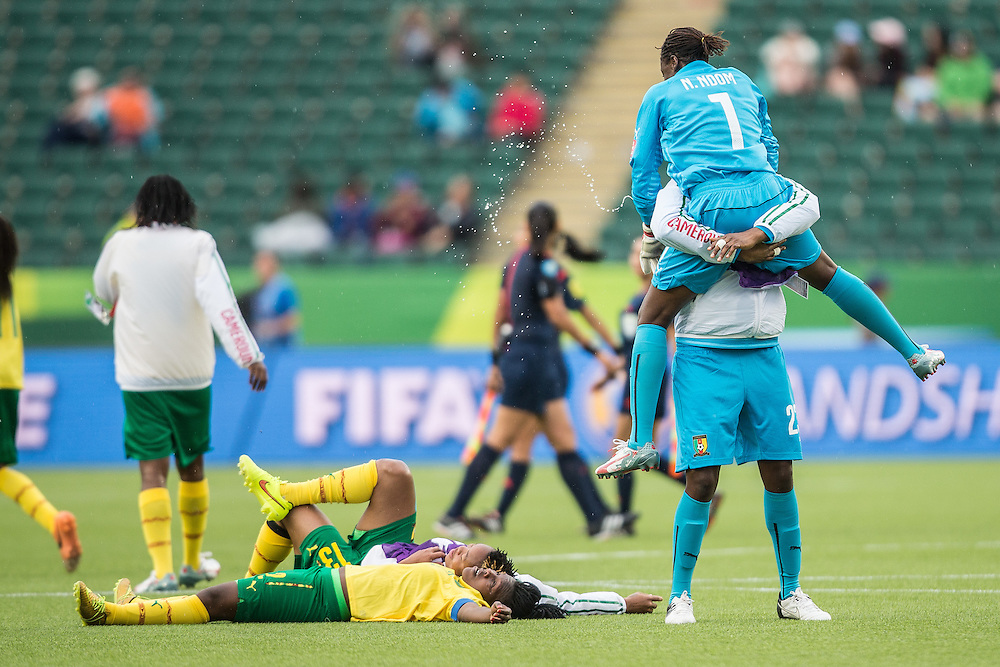 Cameroon's goalkeeper Annette Ngo Ndom  is hoisted by teammate Flore Enyegue as they celebrate their team's 2-1 win over Switzerland in their FIFA Women's World Cup group C match at Commonwealth Stadium in Edmonton, Canada on June 16, 2015.   AFP PHOTO/GEOFF ROBINS