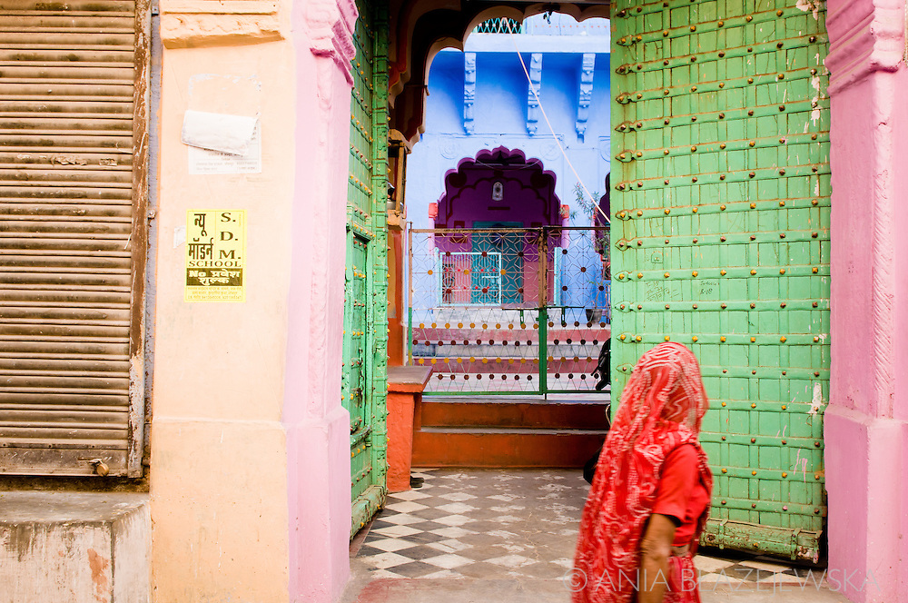 """India, Jodhpur. A woman wearing a red sari walking near the colorful walls of the old Jodhpur, """"the blue city"""" of India."""