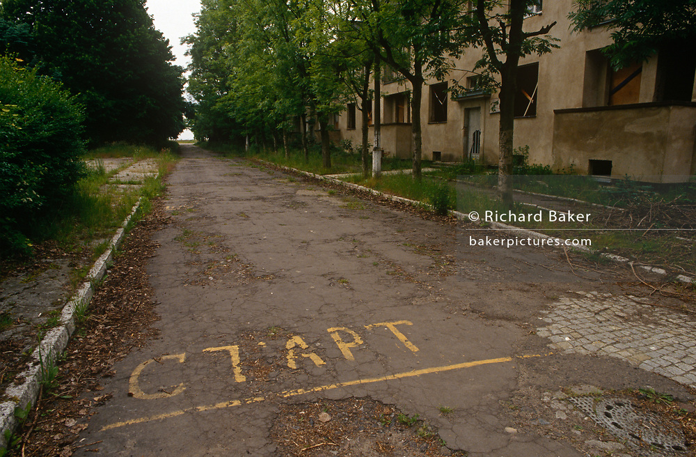 A deserted landscape of a street and overgrown paths and empty housing in the former Russian Soviet army camp in occupied East Germany (ex-GDR/DDR), on 16th June 19990, on Halb Insel Wustrow, near Rostock, Germany. Wustrow was once a WW2 German anti-aircraft artillery position then housing civilian refugees before the eventual Soviet occupation of the former DDR during the Cold War, up until 1990 and the fall of communism and the Berlin Wall. The camp was ransacked and all its assets stripped before its desertion that summer and is a reminder of a fallen ideology