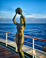 Bronze statue of a woman holding a bowl over her head in the early morning sun. Aft deck of the MV World Odyssey crossing the Pacific Ocean. Semester at Sea, 2016 Spring Semester Voyage. Day 3 of 102. Image taken with a Leica T camera and 23 mm f/2 lens (ISO 100, 23 mm, f/3.5, 1/250 sec).