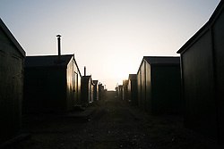 © Licensed to London News Pictures. 13/03/2014<br /> <br /> South Gare, Teesside, England, UK<br /> <br /> Early morning sun lights up the small huts of South Gare Fishermen's Association on the mouth of the River Tees on Teesside.<br /> <br /> Photo credit : Ian Forsyth/LNP