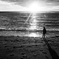 A lone child standing on a beach with crashing waves and long shadows.