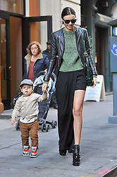 (UK RIGHTS ONLY) Supermodel Miranda Kerr wearing a leather bikers jacket, green jumper and a long black skirt showing her leg like Angelina style, out with her son Flynn in New York. NYC, USA. 21/11/2012<br />