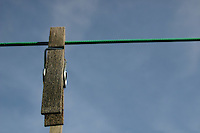 old wooden clothes peg on washing line against blue sky
