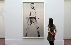 © Licensed to London News Pictures. 12/04/2012. London, UK . A woman stands  in front Andy Warhol's picture of Elvis which is expected to fetch 30 - 50 million US dollars. Photocall for Sotheby's Impressionist and Modern Art Evening Sale 12 April 2012. Photo credit : Stephen Simpson/LNP