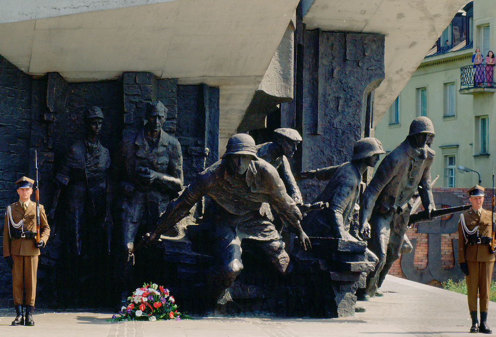 Soldiers standing at attention and holding rifles as they guard the Warsaw Uprising Monument in Poland.
