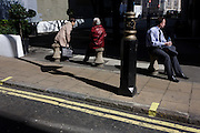 Three people rest in spring sunshine on three concrete bollards in a central London street.