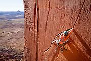 Mary Eden onsights Run Like Hell, a fun traversing 5.10- crack at The Wall.<br /> Indian Creek, Utah