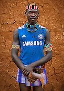 The football stars of tomorrow<br /> <br /> Thousands of Football shirts of Arsenal, Manchester, Chelsea, Milano, etc end up their carreer in... Ethiopia. Sold in the deep south, in the Omo Valley, those second hand clothes are bought by the local tribes. Most of them ignore the meaning of those shirts, and just buy them for the color, the logo, or the shape.<br /> No warrior will go out without his little pillow/seat.<br /> Some, like in Hamer tribe wear at the top of the head a clay helmet where they can put some ostrich feathers when they make a special action, like killing a wild animal, or...a man.<br /> Those tribes won&rsquo;t exist in few years as the ethiopian governement has launched a huge plan to develop the area.<br /> Soon, a highway coming from Mombassa - Nairobi will pass thru the villages to reach Addis Ababa.<br /> <br /> Photo shows: Bana tribe- Chelsea FC<br /> &copy;Eric Lafforgue/Exclusivepix Media