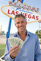 Mid-adult man holding notes in front of Welcome to Las Vegas sign, portrait