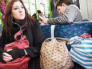 Young woman listening to music on a iPod. On the tube, London 2009